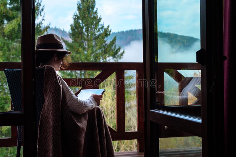 Młoda kobieta podróżnik siedzi przy tarasem z pastylką przeciw pięknej halnej scenerii podczas podróży obraz stock