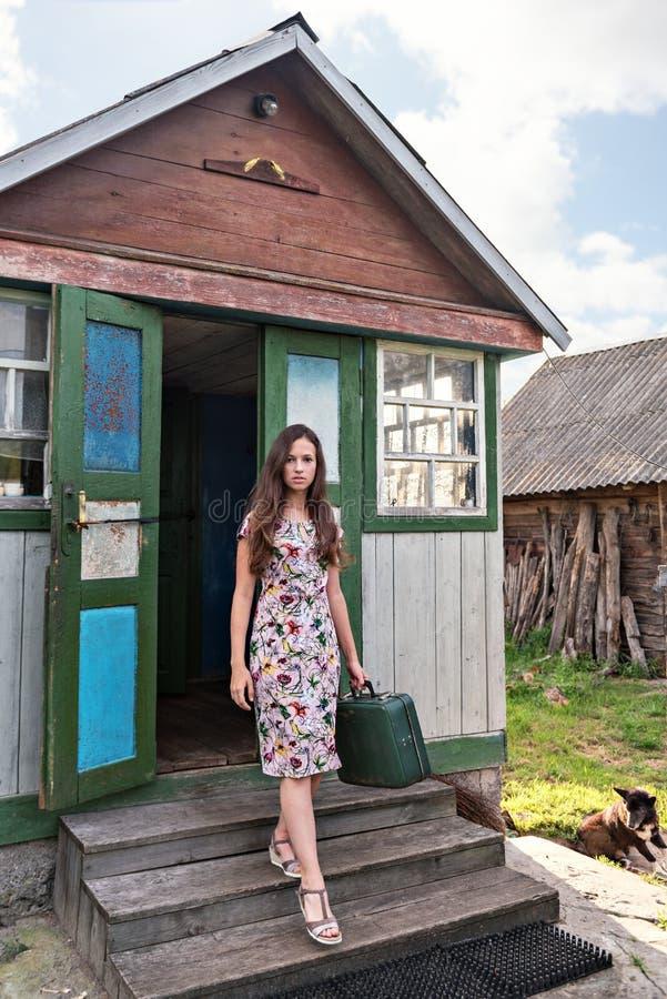 Młoda kobieta podróżnik w retro rocznik sukni z starym walizki przybyciem z starego podławego wieśniaka domu z tłem aband obraz stock