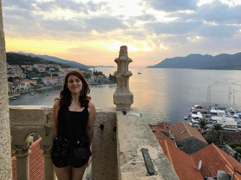 Młoda kobieta podziwia widok od wierzchołka podczas zmierzchu piękny antyczny miasteczko dzwonkowy wierza w miasteczku Korcula fotografia royalty free