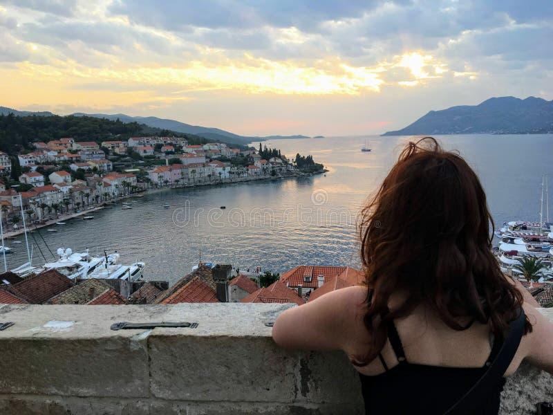 Młoda kobieta podziwia widok od wierzchołka podczas zmierzchu piękny antyczny miasteczko dzwonkowy wierza w miasteczku Korcula obrazy stock