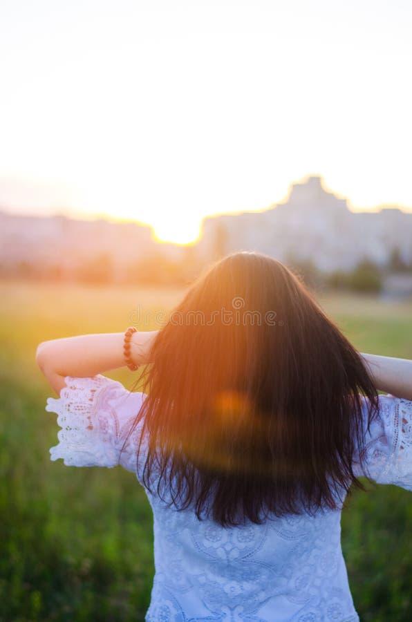 Młoda kobieta podziwia zmierzchu widok z powrotem plenerowy Lato rywalizuje zdjęcia stock