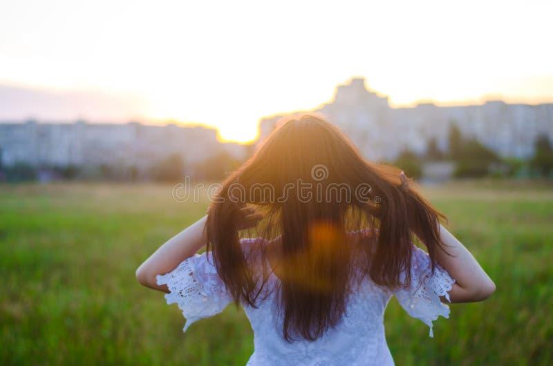 Młoda kobieta podziwia zmierzchu widok z powrotem plenerowy Lato rywalizuje obraz stock
