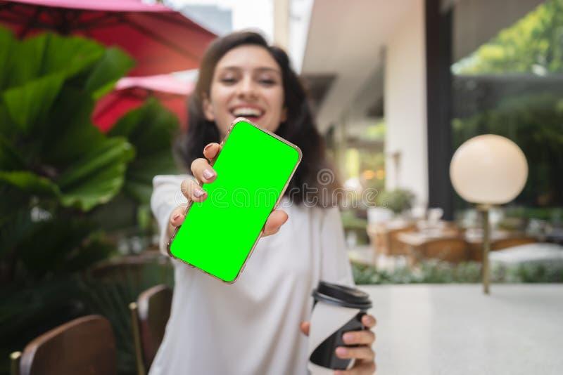 Młoda kobieta pokazuje nowożytnego złocistego smartphone z zieleń ekranem dla zastępstwa fotografia stock