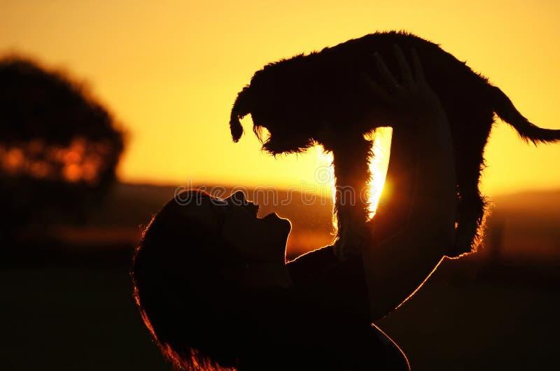 Młoda kobieta pokazuje radość & szczęście gdy przegrany szczeniaka pies zakłada skrytkę