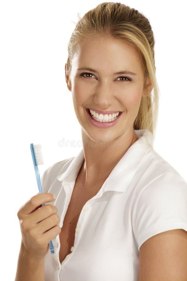 Młoda kobieta pokazywać zębu muśnięcie obraz royalty free