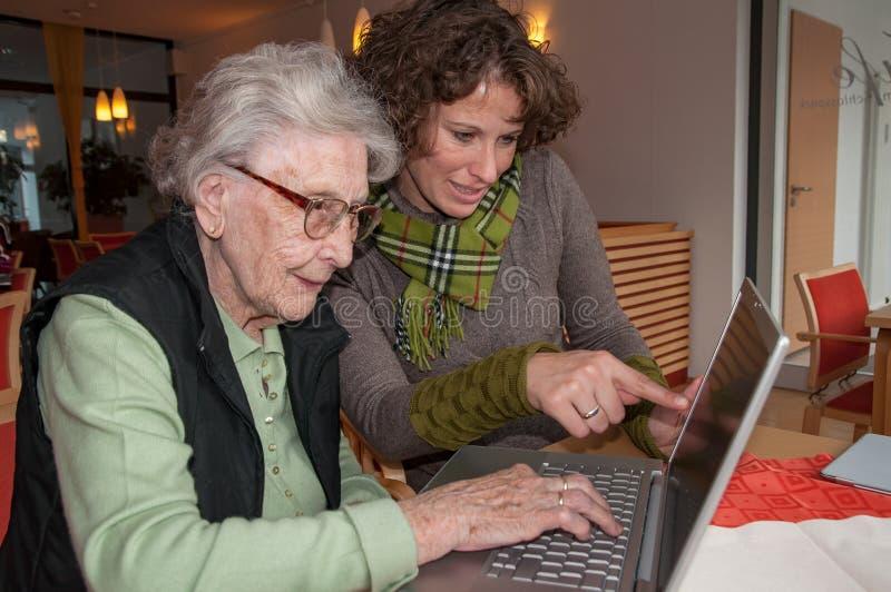 Młoda kobieta pomaga starszej kobiety pracuje z laptopem zdjęcie stock
