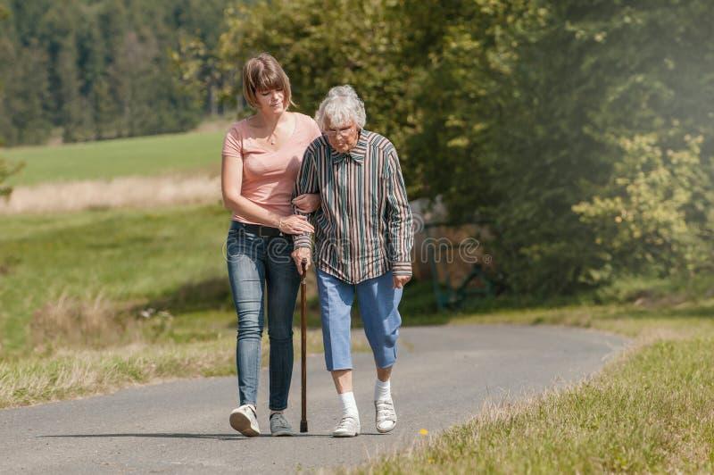 Młoda kobieta pomaga starszemu kobiety odprowadzeniu z kijem zdjęcia stock
