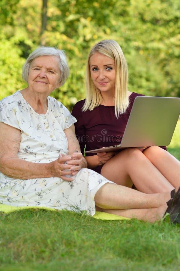 Młoda kobieta pomaga starszemu use laptop obraz royalty free