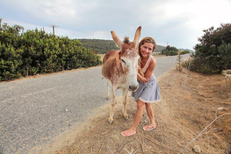 Młoda kobieta pozuje blisko asfaltowej drogi z dzikim osłem, daje on uściśnięciu Te zwierzęta wędrują wolno w Karpass regionie Pó obraz stock
