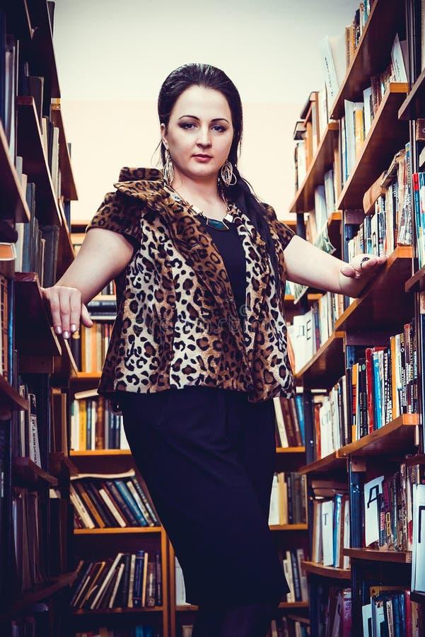 Młoda kobieta pozuje dla kamery przy biblioteką fotografia stock