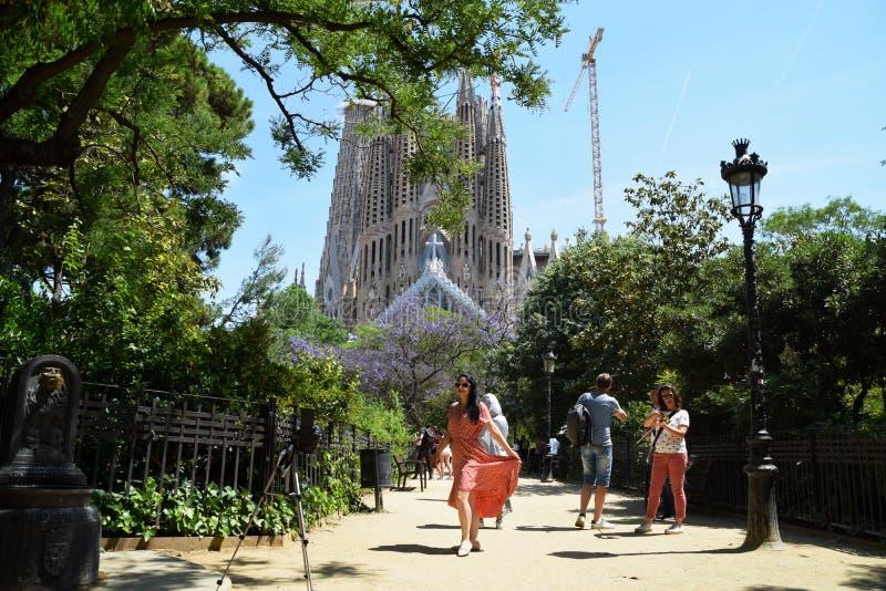 Młoda kobieta pozuje przed kamerą z sławnym katedralnym losem angeles Sagrada Familia w tle zdjęcia stock