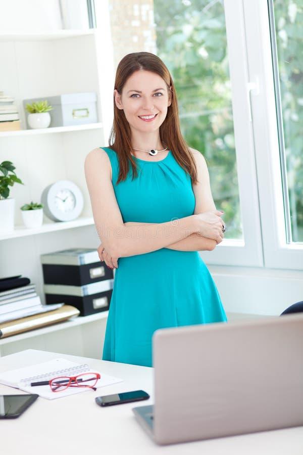 Młoda kobieta pozuje w biurze zdjęcia royalty free