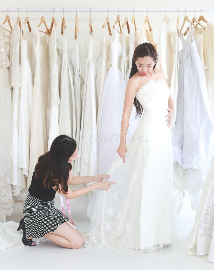 Młoda kobieta próbuje ślubną suknię w studiu, projektant jest jak obraz royalty free