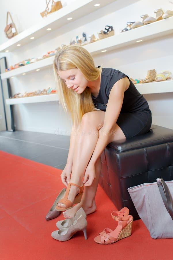 Młoda kobieta próbuje na para butach zdjęcia stock