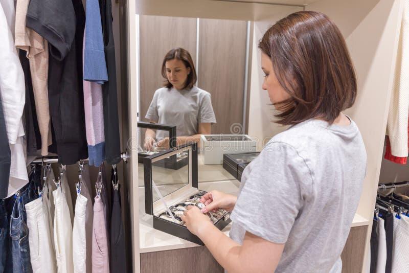 Młoda kobieta próbuje wristwatch w wardobe obraz stock