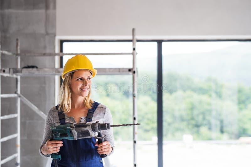Młoda kobieta pracownik z elektrycznym świderem na budowie zdjęcie royalty free