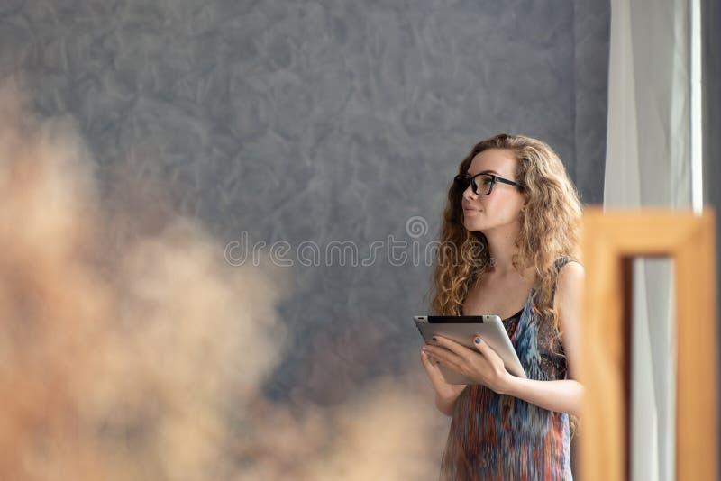 Młoda kobieta pracuje na cyfrowym pastylka komputerze w domu zdjęcie royalty free