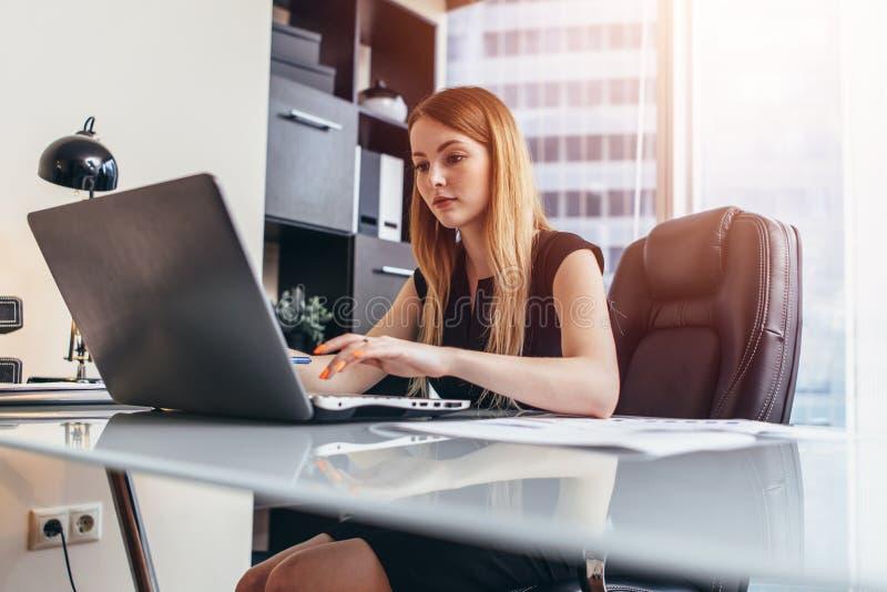 Młoda kobieta pracuje na laptopie studiuje pieniężnych dane i statystyki firma obraz stock