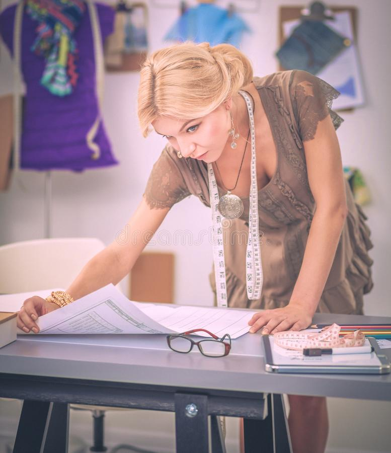 Młoda kobieta projektant mody pracuje przy studiiem zdjęcia stock