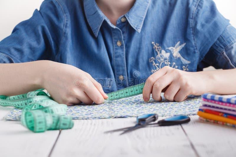 Młoda kobieta projektanta lub krawcowej działanie jako projektanci mody, Wybiera przędze szwalny tkaniny, zawodu i pracy zajęcie, zdjęcia royalty free