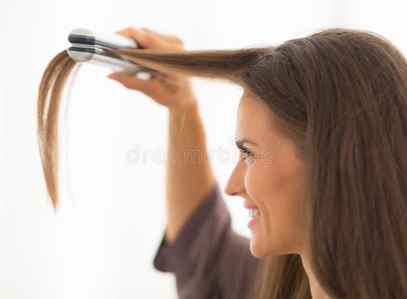 Młoda kobieta prostuje włosy w łazience zdjęcia stock