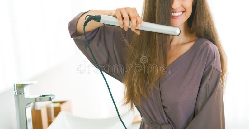 Młoda kobieta prostuje włosy w łazience fotografia stock