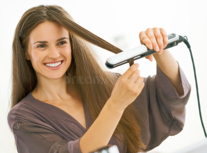 Młoda kobieta prostuje włosy z prostownicą zdjęcia stock