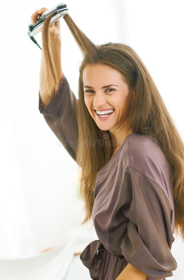 Młoda kobieta prostuje włosy z prostownicą obraz stock