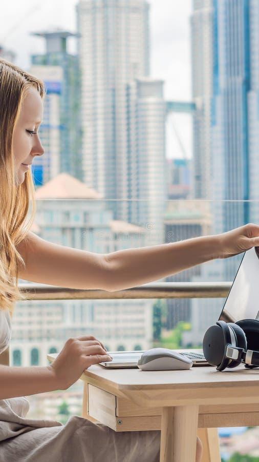 Młoda kobieta przegapia drapacze chmur pracuje na laptopie na jej balkonie Freelancer, daleka praca, praca od domu obrazy stock