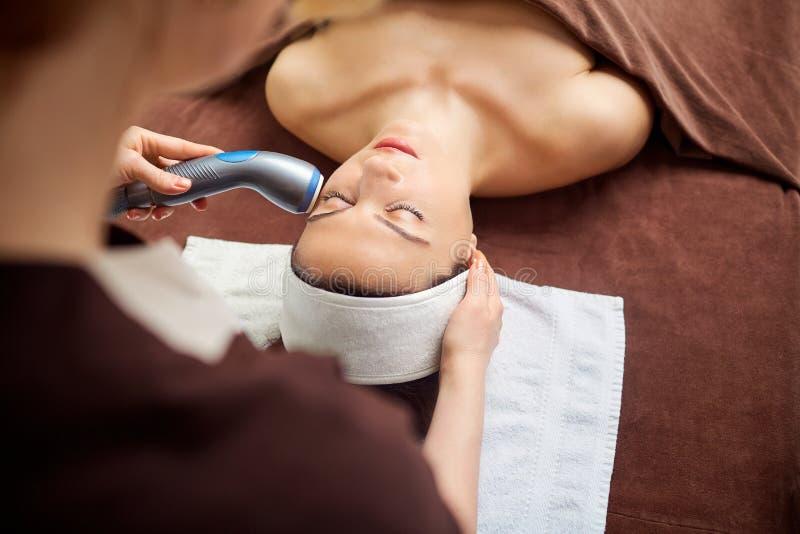 Młoda kobieta przy kosmetyczką w zdroju pokoju zdjęcie stock