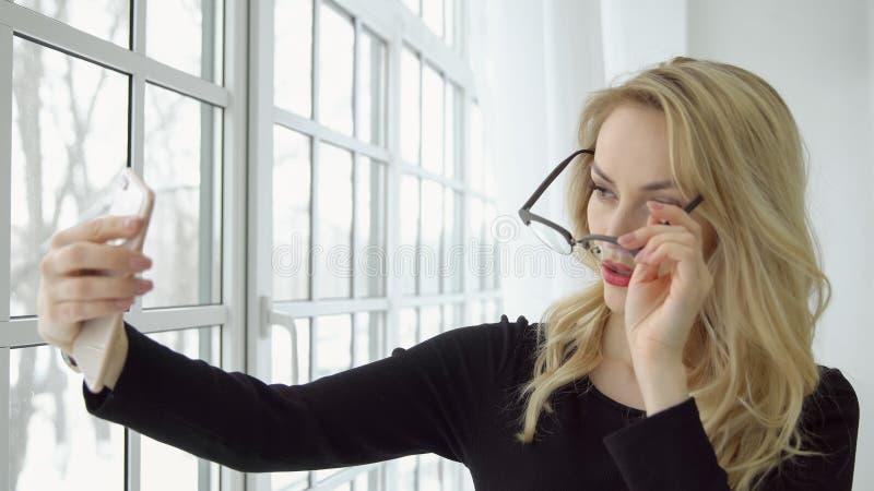 Młoda kobieta przy okno bierze obrazki ona na telefonie z frontową kamerą obraz stock