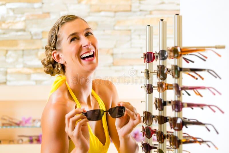 Młoda kobieta przy okulisty zakupy okularami przeciwsłonecznymi obrazy royalty free