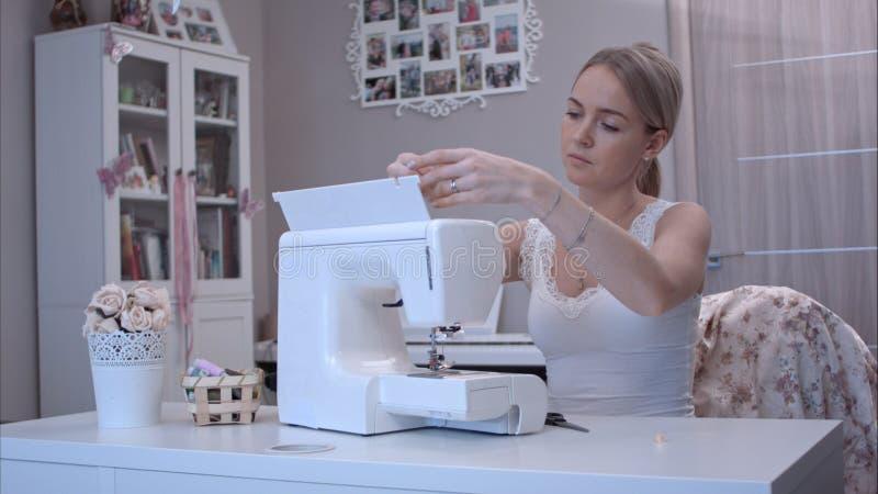 Młoda kobieta przygotowywa jej szwalną maszynę obraz stock