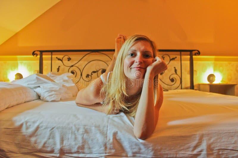 Młoda kobieta relaksująca i ono uśmiecha się na łóżku fotografia stock