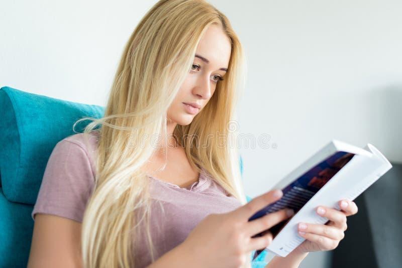 Młoda kobieta relaksuje na kanapie w domu, czytający książkę obraz stock