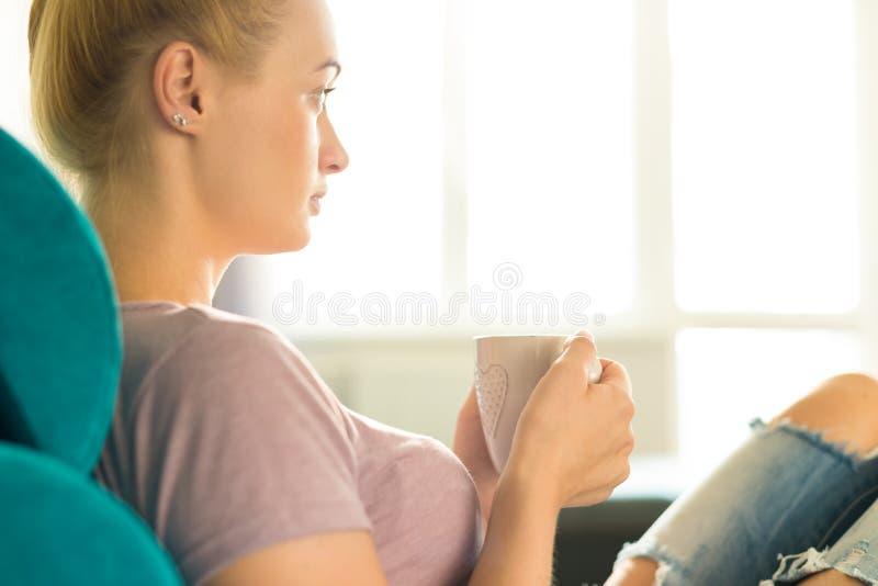 Młoda kobieta relaksuje na kanapie w domu, ogląda tv i cieszy się kawę, obraz royalty free