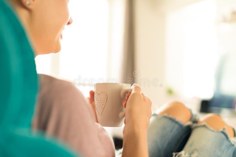 Młoda kobieta relaksuje na kanapie w domu, ogląda tv i cieszy się kawę, zdjęcia royalty free