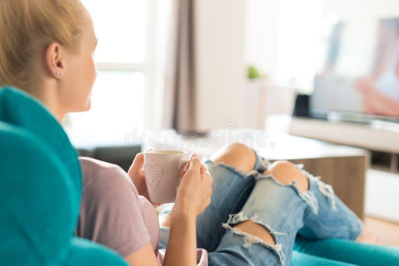 Młoda kobieta relaksuje na kanapie w domu, ogląda tv i cieszy się kawę, obrazy stock
