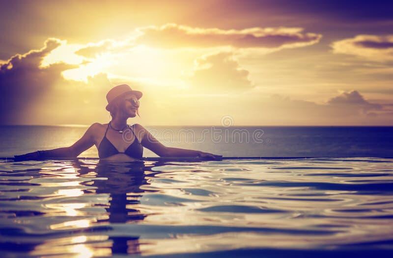 Młoda kobieta relaksuje na pływackim basenie, blisko morza w zmierzchu obraz royalty free
