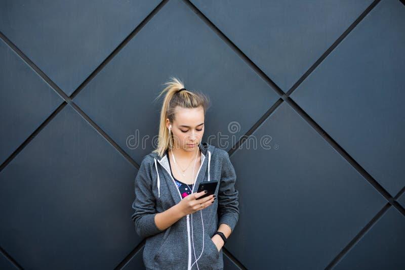 Młoda kobieta relaksuje po jogging, słuchania używać jej mądrze telefon muzyka i Pisać na maszynie wiadomość opiera przeciw czern obrazy royalty free