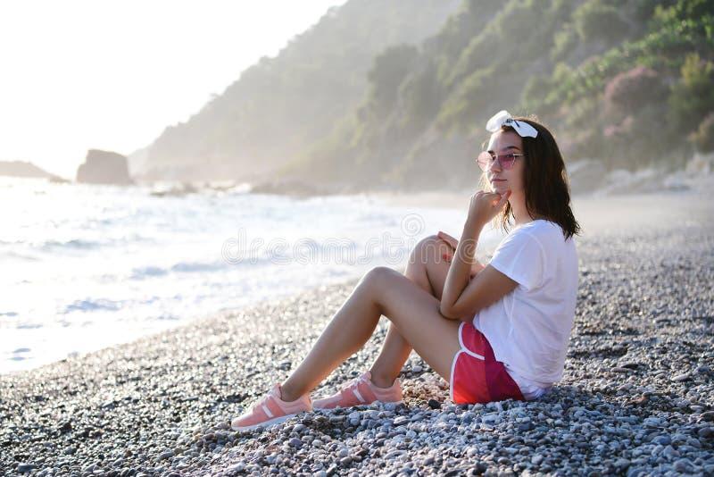 Młoda kobieta relaksuje przy otoczak plażą przy morzem śródziemnomorskim zdjęcie royalty free