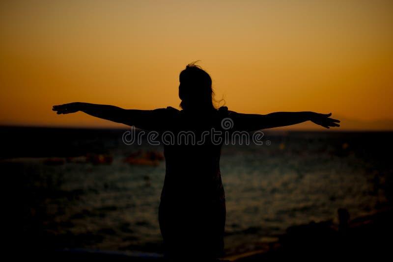 Młoda kobieta relaksuje w lato zmierzchu obrazy stock