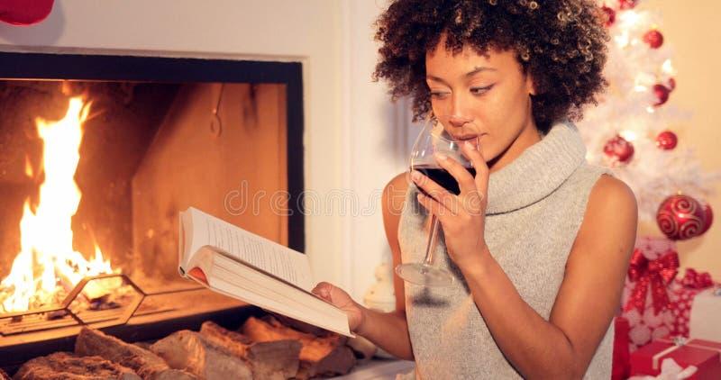 Młoda kobieta relaksuje z czerwonym winem i książką zdjęcie royalty free