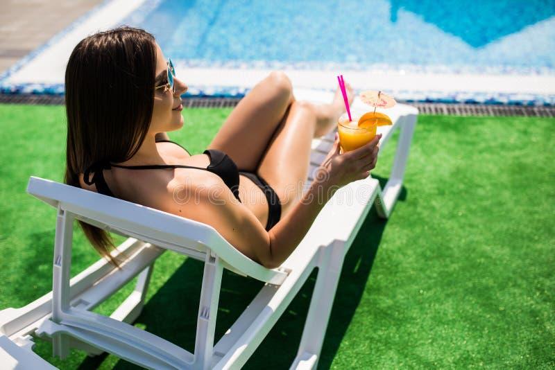 Młoda kobieta relaksuje z koktajlem na bryczka pobliskim basenie w słonecznym dniu w swimsuit zdjęcie royalty free