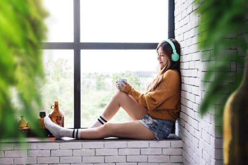 Młoda Kobieta Relaksuje z muzyką Od hełmofonu w Wygodnym Domowym Niedalekim okno, Cieszy się z ranku światłem słonecznym obraz stock