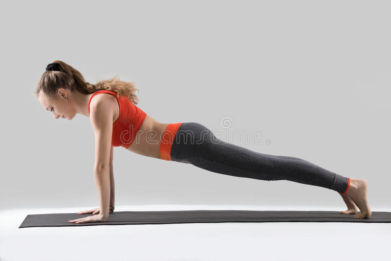 Młoda kobieta robić Pcha podnosi lub prasa podnosi, studio zdjęcie stock