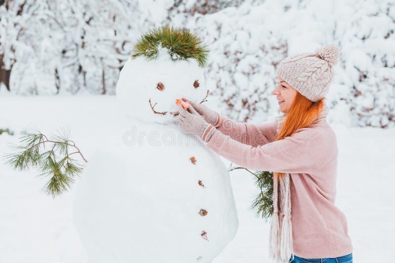 Młoda kobieta robi bałwanu w parku zdjęcia stock