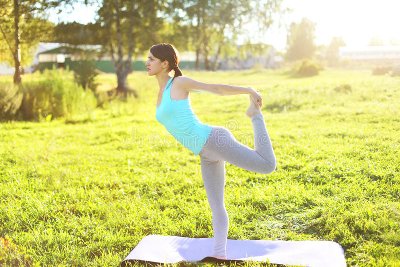 Młoda kobieta robi joga rozciąga ćwiczenia na trawie w pogodnym letnim dniu obraz royalty free