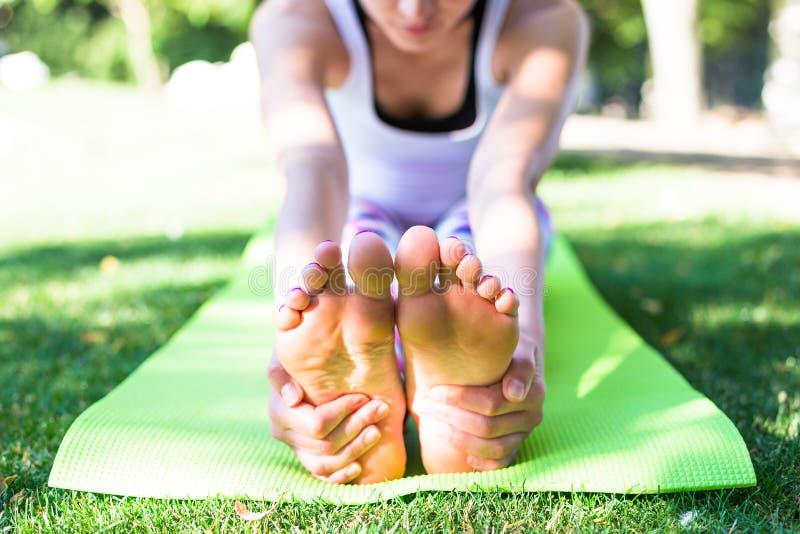 Młoda kobieta robi joga w ranku parku blisko jeziora fotografia royalty free