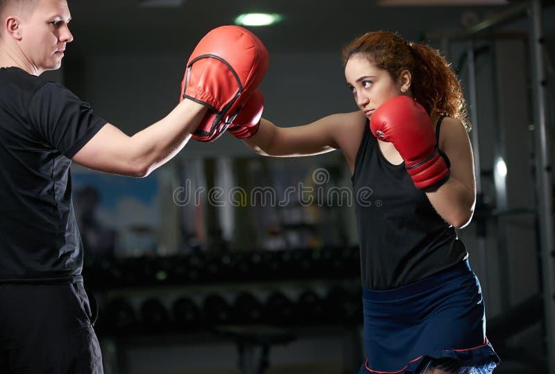Młoda kobieta robi kickboxing trenować z jej trenerem obrazy royalty free